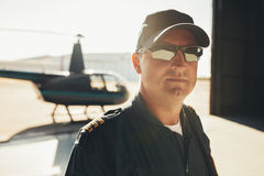 Professional pilot standing in airplane hangar Royalty Free Stock Photos