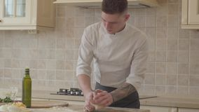 Professional pizza maker in cook uniform skillfully and fast kneeding dough for pizza in modern kitchen. Olive oil. Hands of young pizza maker in cook uniform stock video footage
