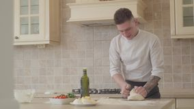 Professional pizza maker in cook uniform skillfully and fast kneeding dough for pizza in modern kitchen. Olive oil. Young pizza maker in cook uniform skillfully stock video