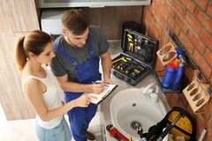 Professional plumber with female client near kitchen sink. Professional plumber with client near kitchen sink royalty free stock photography