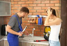 Professional plumber with female client near kitchen sink. Professional plumber with client near kitchen sink royalty free stock image