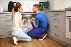 Professional plumber with female client near kitchen sink. Professional plumber with client near kitchen sink stock photos