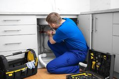Professional plumber fixing kitchen sink. Professional plumber in uniform fixing kitchen sink royalty free stock images