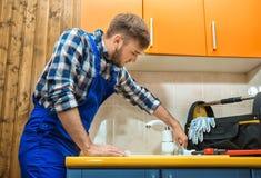 Professional plumber fixing kitchen sink. Professional plumber in uniform fixing kitchen sink stock photo