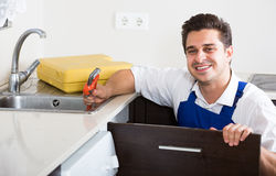 Professional plumber fixing problems in domestic kitchen Royalty Free Stock Photos