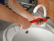 Professional plumber fixing sink in kitchen. Closeup stock photo