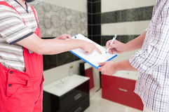 Professional plumber giving his client the contract document. For signing after bathroom reparation Royalty Free Stock Photography