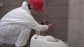 Professional plumber man preparing for toilet pan bowl mount in new bathroom. Static shot. 4K stock video