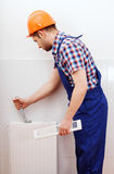 Professional plumber repairing white radiator Stock Photography