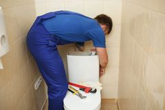 Professional plumber in uniform fixing toilet tank. Indoors royalty free stock images