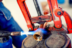 Professional plumber welding copper and fittings with blowtorch Royalty Free Stock Images