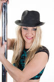 Professional poledancer  girl with  black hat performs tricks on a pole. Royalty Free Stock Image