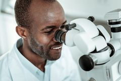 Professional positive doctor reviewing patient with special microscope stock images