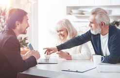 Professional positive insurance agent meeting with elderly couple stock photos