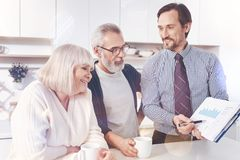 Professional positive real estate agent showing graph to elderly couple royalty free stock photos