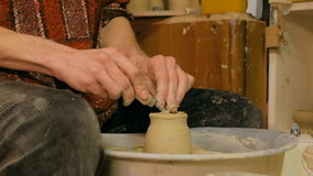 Professional potter carving mug with special tool in pottery workshop stock footage