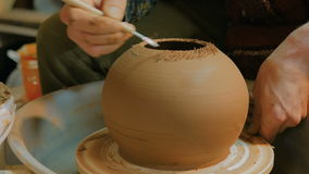 Professional potter carving mug with special tool in pottery workshop stock video
