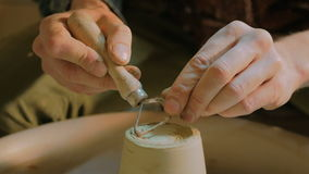 Professional potter carving mug with special tool in pottery workshop stock video footage