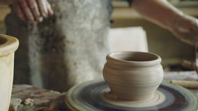 Professional potter is making clayware on potter`s wheel, looking at half-finished pot and checking quality of work. Professional male potter is making clayware stock footage