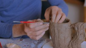 Professional potter making pattern on clay mug with special tool in workshop. Professional potter making pattern on clay mug with special tool in pottery stock footage