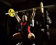 Professional powerlifter lifts the bar above his head in a squat. Rod push. Mixed media Royalty Free Stock Photography