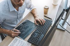 Professional programmer working at developing programming and website working in a software develop company office, writing codes. And typing data code stock image