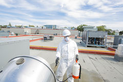 Professional in protective uniform, mask, gloves in the roof for cleaning Royalty Free Stock Photography