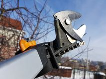 Professional pruner with tensioner and chain for trimming trees against the sky royalty free stock photos