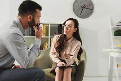 professional psychiatrist and sad patient having consultation royalty free stock images