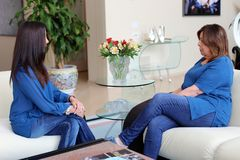 Professional psychologist female doctor dark hair with patient. Mother and daughter sharing a positive time. Royalty Free Stock Photos