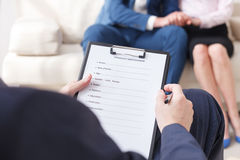 Professional psychologist making notes on therapy session stock photography