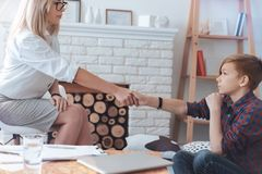 Professional psychotherapist and teenage boy shaking hands in office. I hope we are friends now. Side view on a female therapist trying to build bridges with a Stock Images