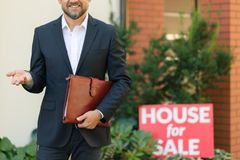 Professional real estate agent. Close-up of professional real estate agent in black suit with leather notebook standing in front of house for sale Stock Photography