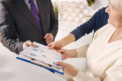 Professional real estate agent making bargain with elderly couple stock images
