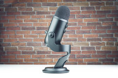 Professional Recording Microphone. On White Table And Red Bricks Wall Background Royalty Free Stock Photography