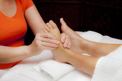 Professional relaxing foot massage, various techniques. Woman receiving a leg and foot massage while lying on a towel in a award winning health massage center Stock Photos