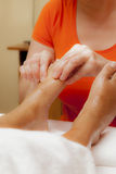 Professional relaxing foot massage, various techniques. Woman receiving a leg and foot massage while lying on a towel in a award winning health massage center Royalty Free Stock Image