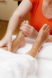 Professional relaxing foot massage, various techniques. Woman receiving a leg and foot massage while lying on a towel in a award winning health massage center Stock Photography