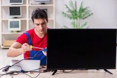 The professional repair engineer repairing broken tv. Professional repair engineer repairing broken tv Stock Images