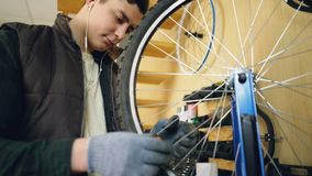 Professional repairman is fixing bicycle wheel spokes straightening them with special tools and rotating wheel to check. Professional repairman is busy fixing stock footage