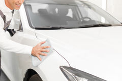 Professional repairman is washing automobile with Royalty Free Stock Images