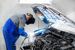 professional repairman worker in automotive industry welding metal body car with sparks Stock Images