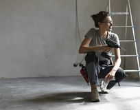 Professional repairwoman posing and holding a drill royalty free stock image