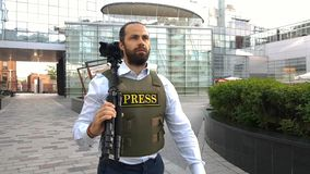 Professional reporter live on city street. A reporter with special clothes walks through the streets of the city