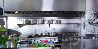 Professional restaurant kitchen stainless steel. Professional restaurant kitchen in stainless steel with vegetables and meat stock photography
