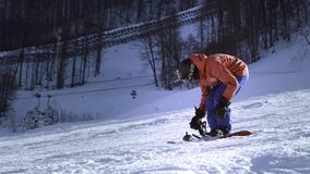 Professional rider puts snowboard on his feet. Button fasteners. Getting ready to ski or snowboard. Enjoys winter sports stock footage