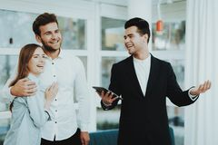 Professional Rieltor Shows A Property To Couple. Professional Rieltor Shows A Property To Young Couple. Making A Contract. Information On Tablet. Panoramic royalty free stock images