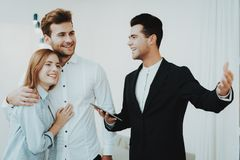 Professional Rieltor Shows A Property To Couple. Professional Rieltor Shows A Property To Young Couple. Making A Contract. Information On Tablet. Panoramic stock photo