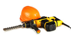 Professional rotary hammer drill and a construction helmet Royalty Free Stock Images
