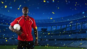 Professional rugby player standing in front of a stadium with confetti falling. Animation of an African American male rugby player holding a ball and looking to stock footage